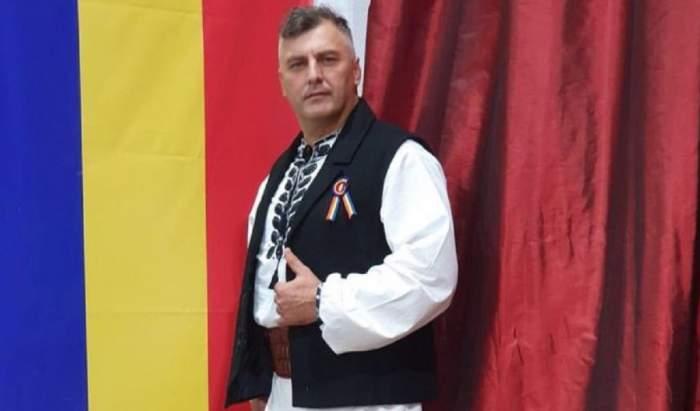 Corin Dobrinescu poartă costum popular, cu ie albă și veste neagră. În spatele lui se află steagul României.