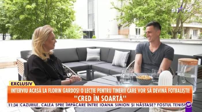 Florin Gardoș dă un interviu de la o terasă pentru Antena Stars. Fotbalistul poartă un tricou gri.