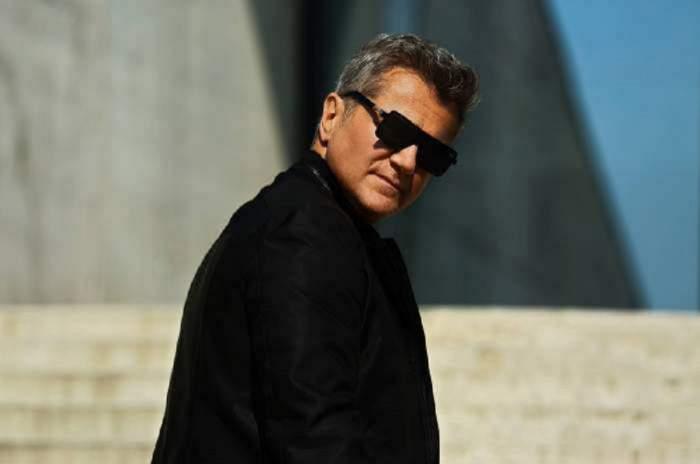 Dan Bittman poartă ochelari de soare și geacă neagră. Artistul este cu spatele la camera foto.