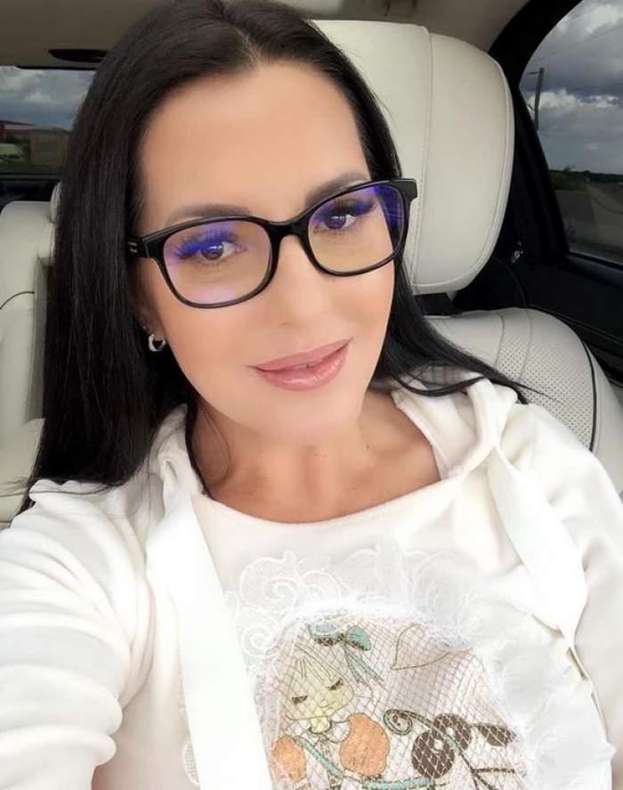 Angela Rusu își face o poză din mașină, purtând ochelari de vedere și bluză albă.