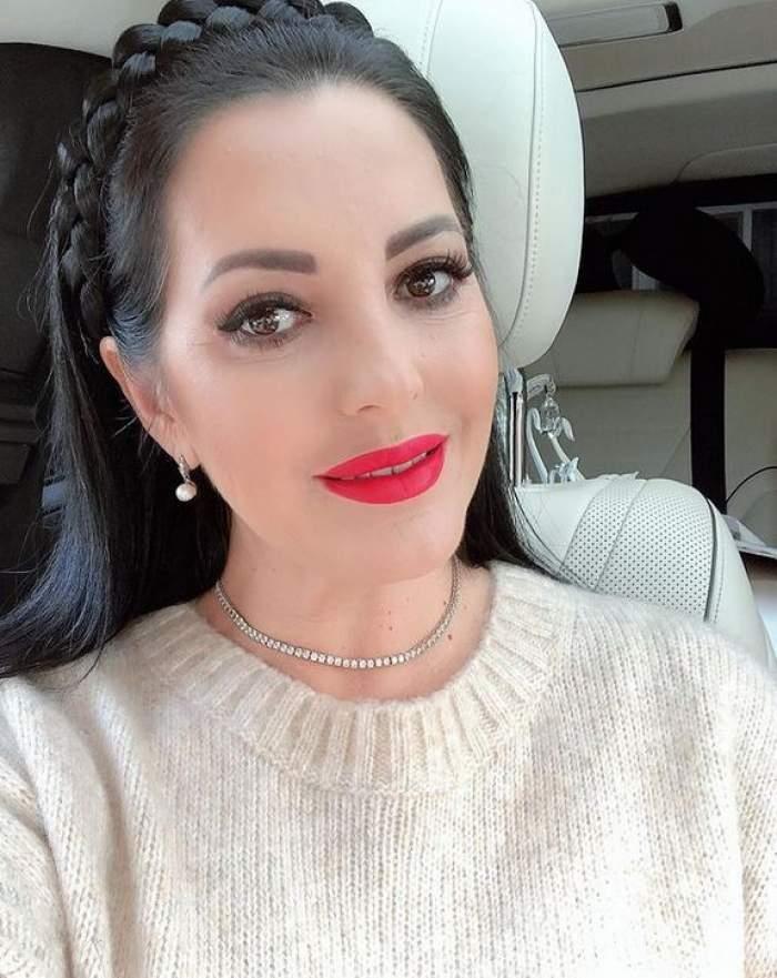 Angela Rusu e în mașină și poartă un pulover crem.