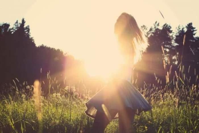 o fata prin iarba, soarele e pe cer