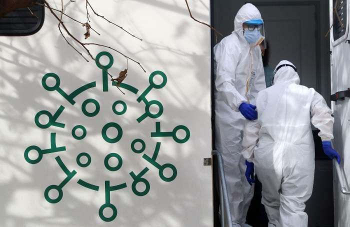 Mai multe cadre medicale poartă combinezon alb, mănuși și mască de protecție.