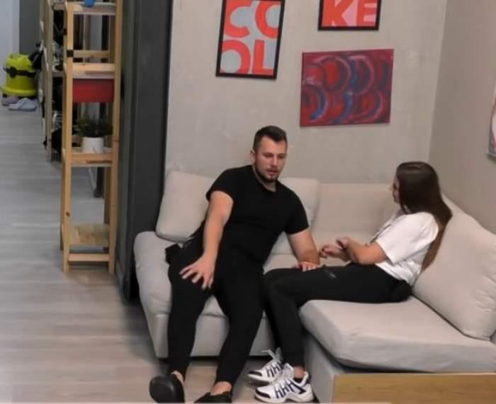 Andreea și Alexandru de la Mireasa discută pe o canapea. Ea poartă tricou alb și pantaloni negri, iar el e îmbrăcat tot în negru.