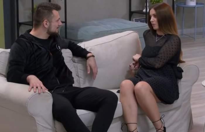 Andreea și Alexandru la emisiunea Mireasa. Cei doi sunt îmbrăcați în negru și stau pe canapea albă.