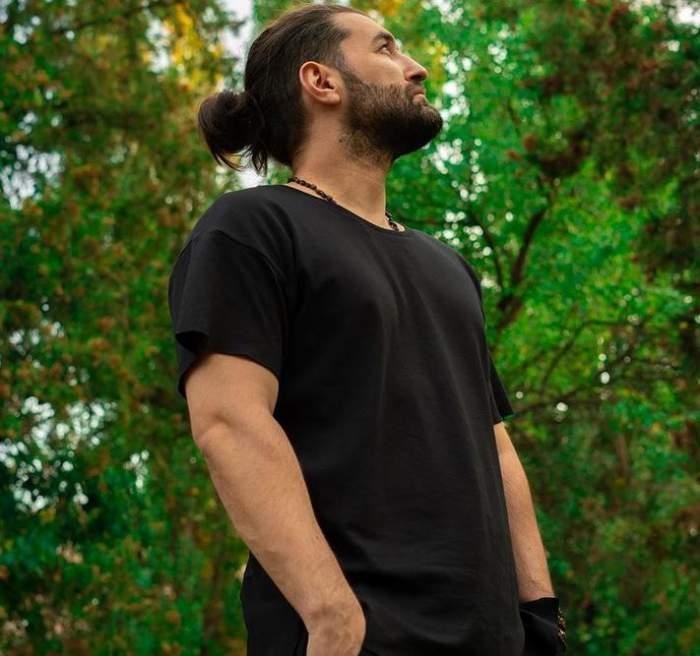 Smiley e îmbrăcat în tricou și pantaloni negri și se află parc. Artistul își ține mâinile în buzunare.