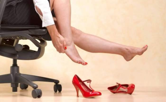 Imagine ilustrativa cu picioarele unei femei ce sta pe scaun, descaltata de pantofii rosii