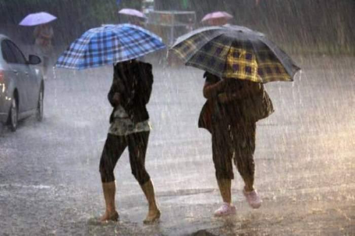 Două femei merg pe stradă și se apără de ploaie cu umbrelele. În spatele lor se vede o mașină.