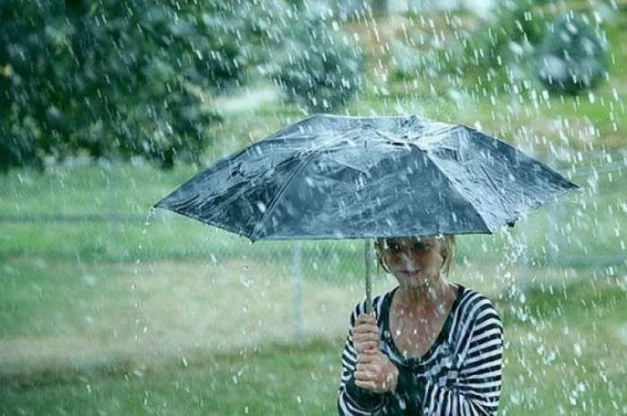 O fetiță merge prin parc și se ferește de ploaie cu umbrela.