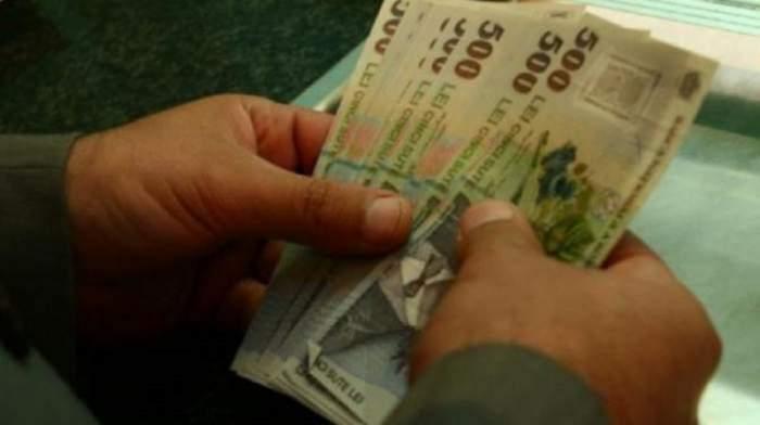 Un om care numără bani, mai exact bancnote de 500 de lei.
