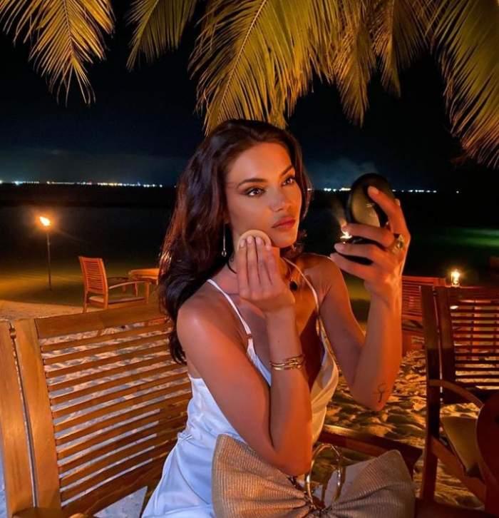 Cristina Ich este la o terasa si se da cu pudra la masa, noaptea