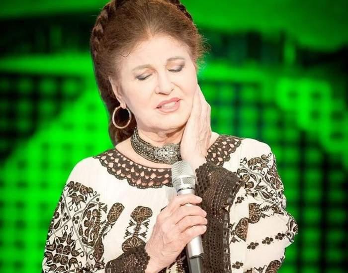 Irina Loghin e pe scenă și cântă la microfon. Artista poartă o ie albă cu motive tradiționale maro.