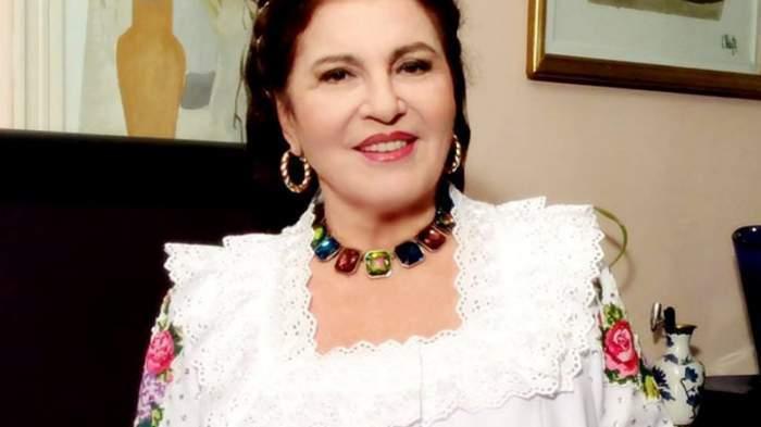 Irina Loghin poartă rochie albă cu motive tradiționale colorate. Artista zâmbește larg.