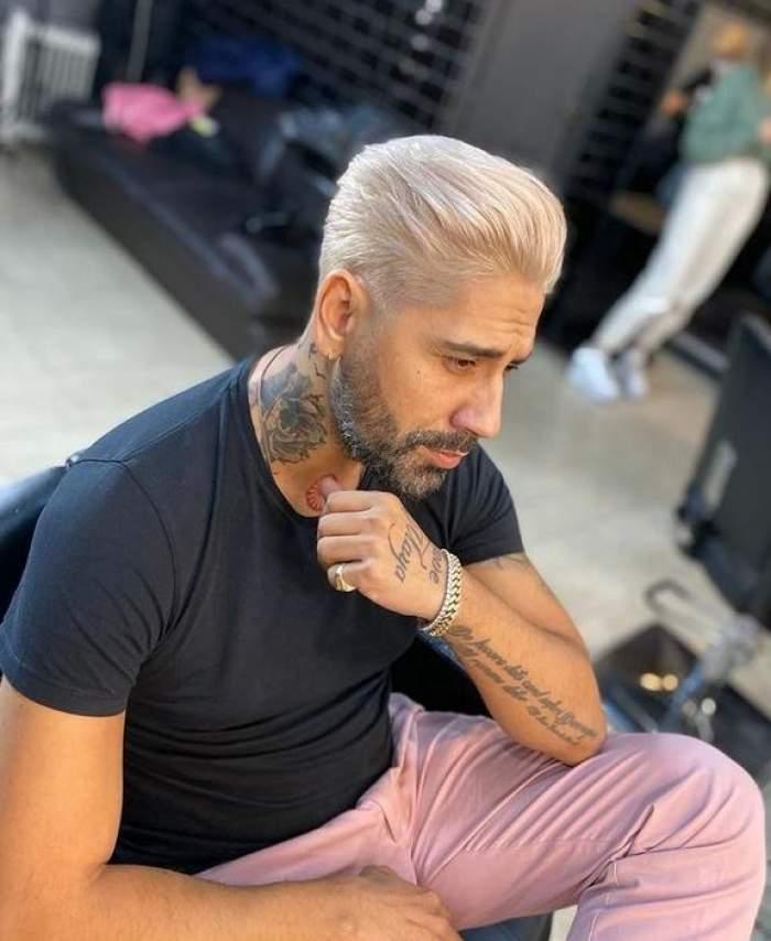 Connect-R poartă un tricou negru și pantaloni roz și stă pe scaun la salonul de frizerie. Artistul privește în oglindă.