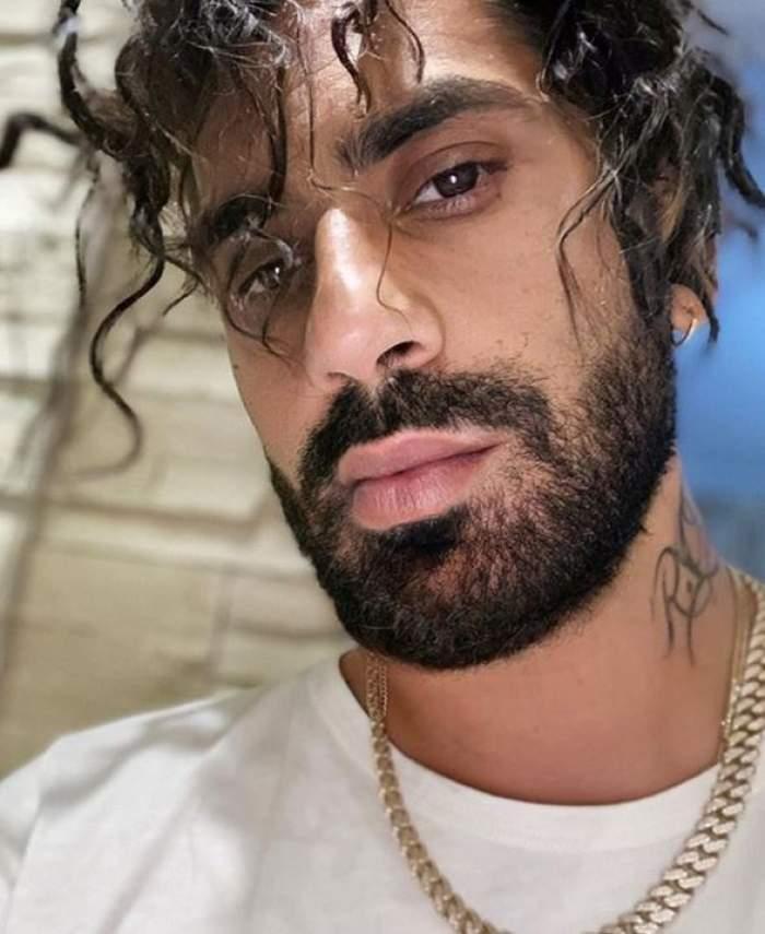 Connect-R într-un selfie. Artistul poartă tricou alb și un lanț auriu la gât.