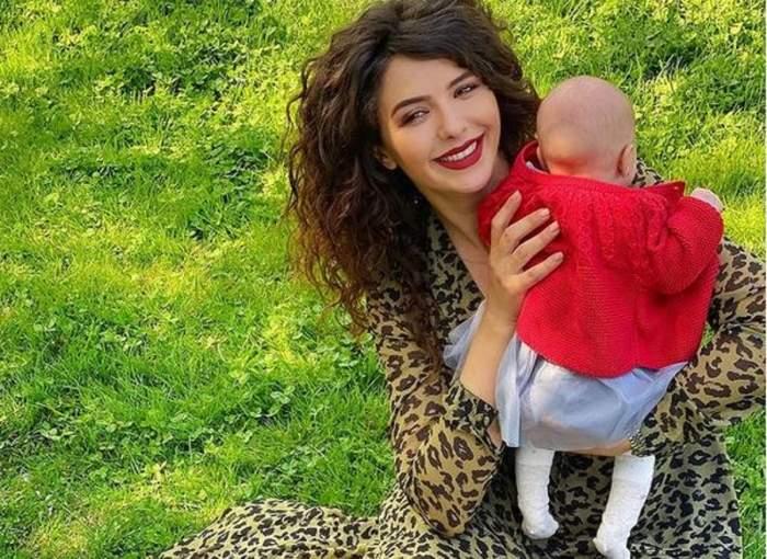 Like Creața de la Chefi la cuțite stă pe iarbă și poartă rochie cu animal print. Vedeta o ține în brațe pe fiica ei, îmbrăcată cu pulover roșu.