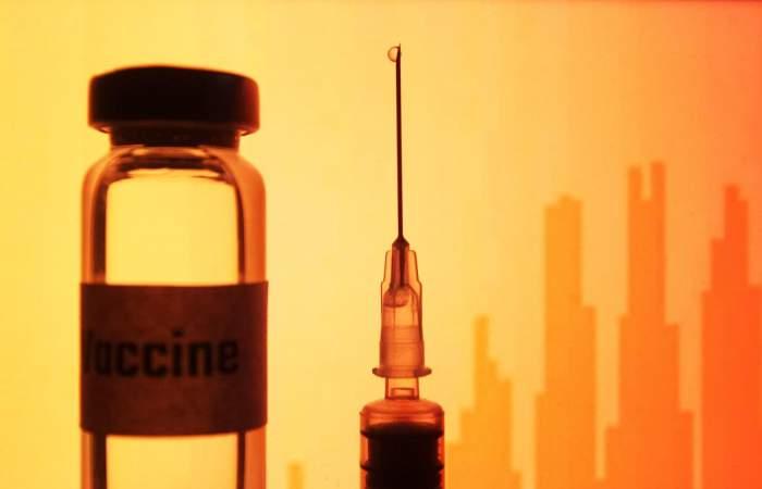Doză de vaccin anti-covid-19 și o seringă.