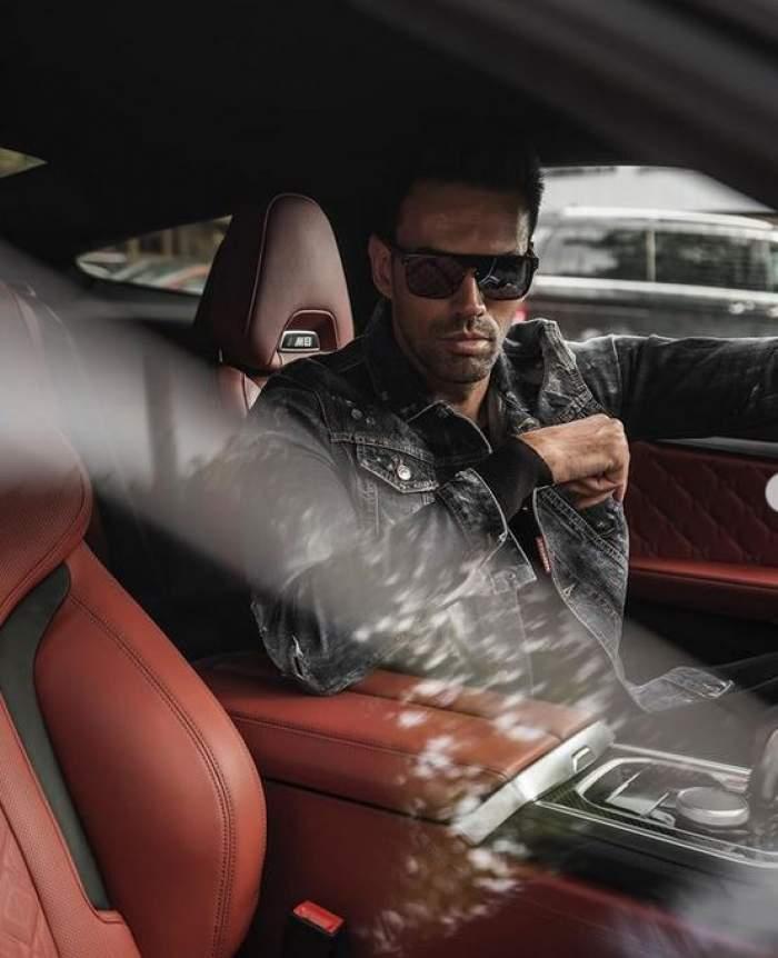 ZED se află mașină. Vedeta poartă ochelari de soare și geacă din piele neagră.