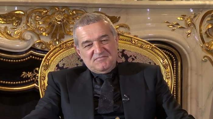 Gigi Becali, p scaun, în costum negru