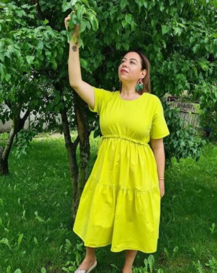 Oana Roman în rochie galbenă, în grădină.