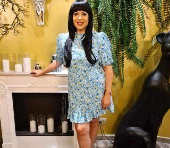 Oana Roman cu perucă brunetă și rochie albastră.