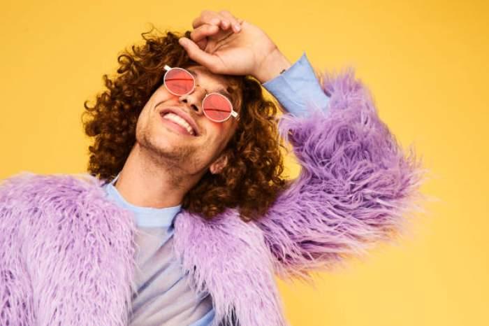 Imagine cu un barbat in haine coloarte si ochelari de soare