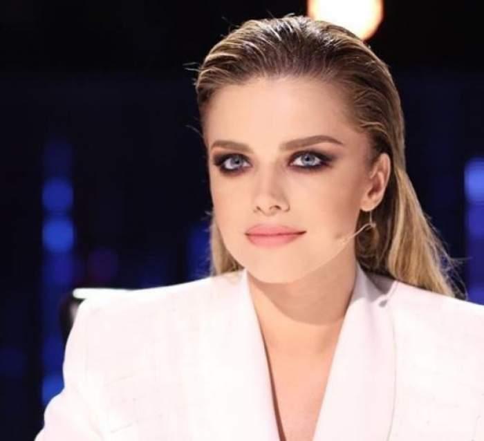 Alexandra Dinu cu sacou alb, într-o emisiune TV.
