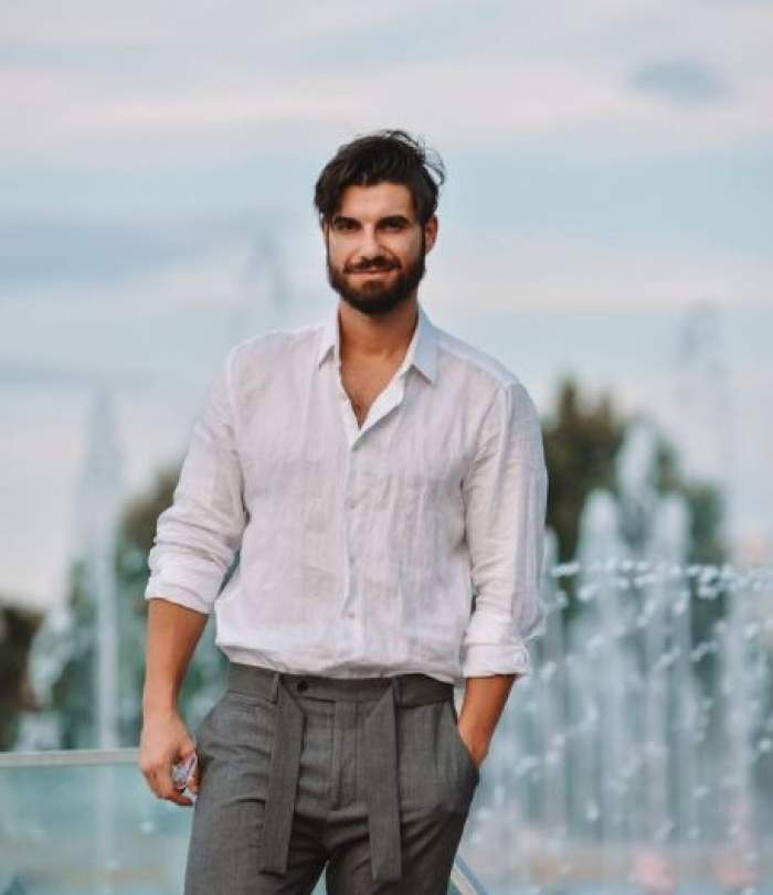 Andi Constantin cu cămașă albă și pantaloni gri.