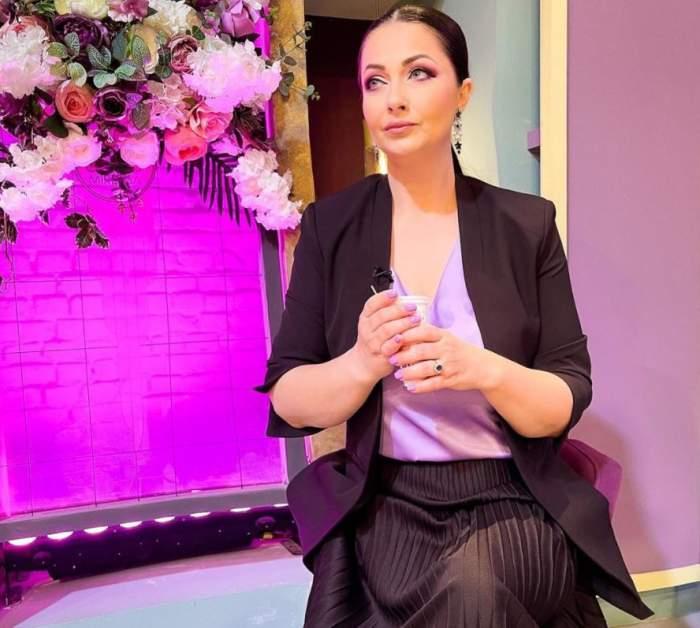 Gabriela Cristea sta pe scaun, are un costum negru cu tricou mov si are parul prins