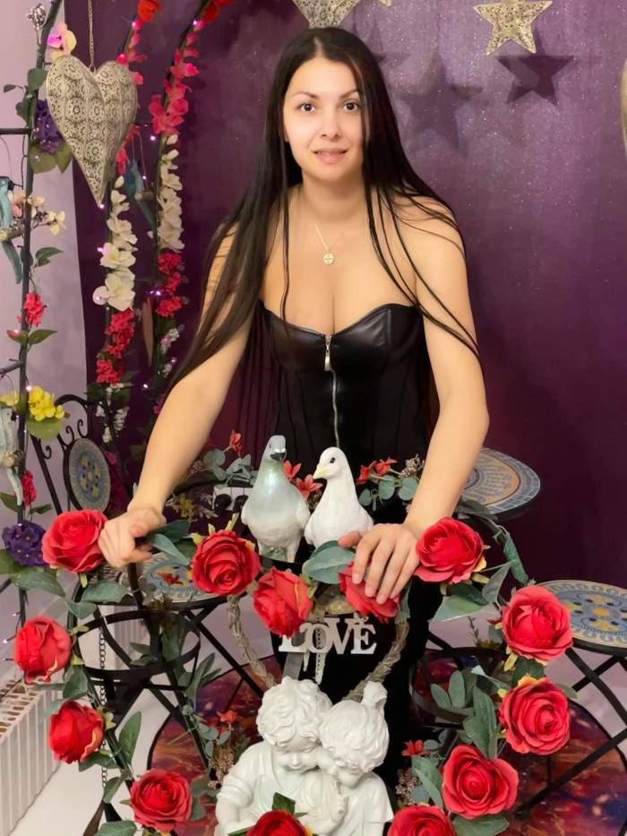 Medana într-un top negru, cu trandafiri în față.