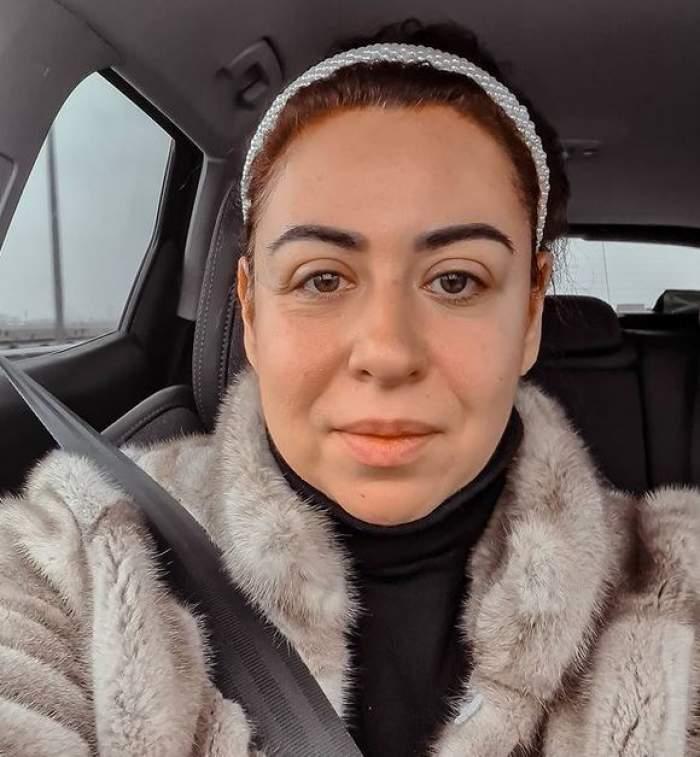 Oana Roman se află în mașină. Vedeta poartă o haină de blană cenușie și zâmbește discret, având pe cap o diademă albă din perle.