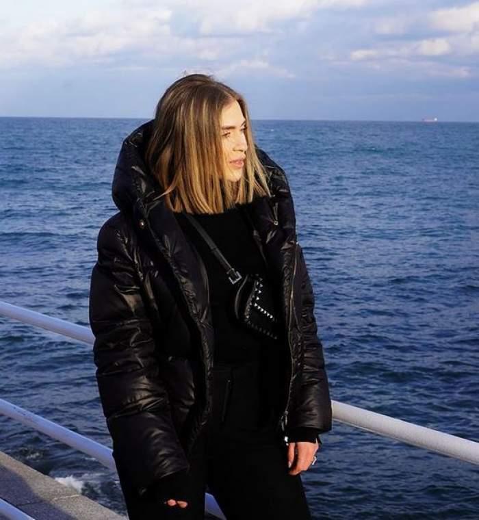 Oana Radu e la mare. Vedeta poartă pantaloni, geacă, bluză și geantă neagră. Artista privește către apă.