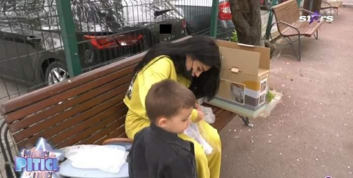 Elena Ionescu stă pe o bancă și poartă un trening galben. Vedeta îi asamblează bicicleta fiului ei. Răzvan poartă o geacă neagră din denim.