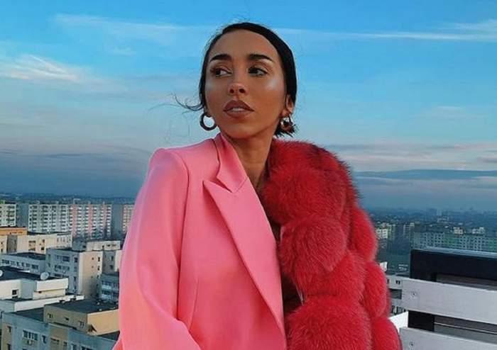 Ruby poartă un sacou roz și se află pe balcon. Vedeta are pe umăr o blană roșie și se uită într-o parte.