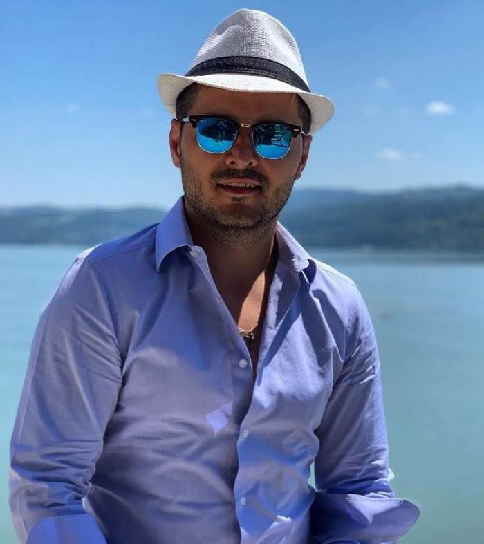 Liviu Vârciu se află la mare. Artistul poartă o pereche de ochelari de soare, o pălărie albă cu dungă neagră și o cămașă bleu.