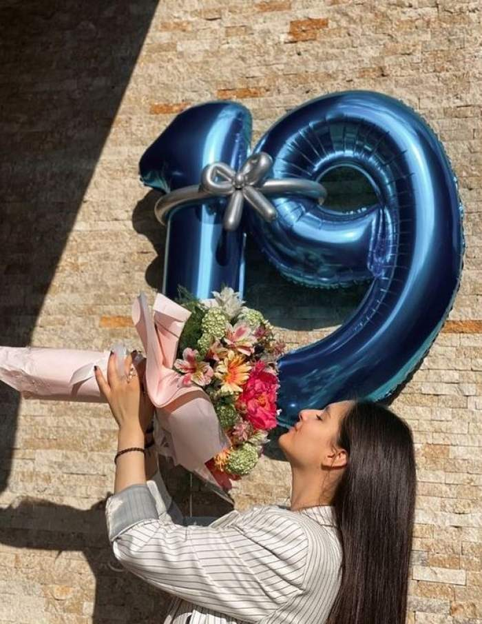 Fiica cea mare a lui Liviu Vârciu poartă un sacou alb cu dungi negre. Carmina ține în mână un buchet de flori colorate și în spatele ei sunt niște baloare albastre cu cifrele 1 și 9.