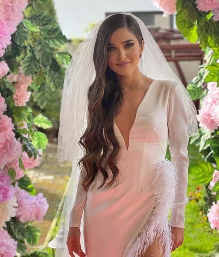 Theo Rose poartă rochie de mireasă albă voal alb. Vedeta zâmbește și în spatele ei sunt mai multe flori roz.