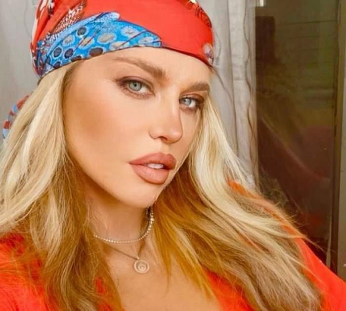 Loredana Groza poartă pe cap batic roșu cu model bleu și e îmbrăcată cu bluză roșie. Vedeta ține gura întredeschisă.