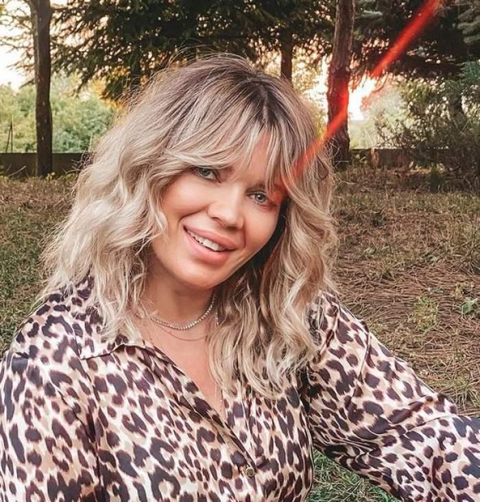 Gina Pistol e îmbrăcată într-o cămașă cu animal print, stil leopard. Vedeta zâmbește larg.