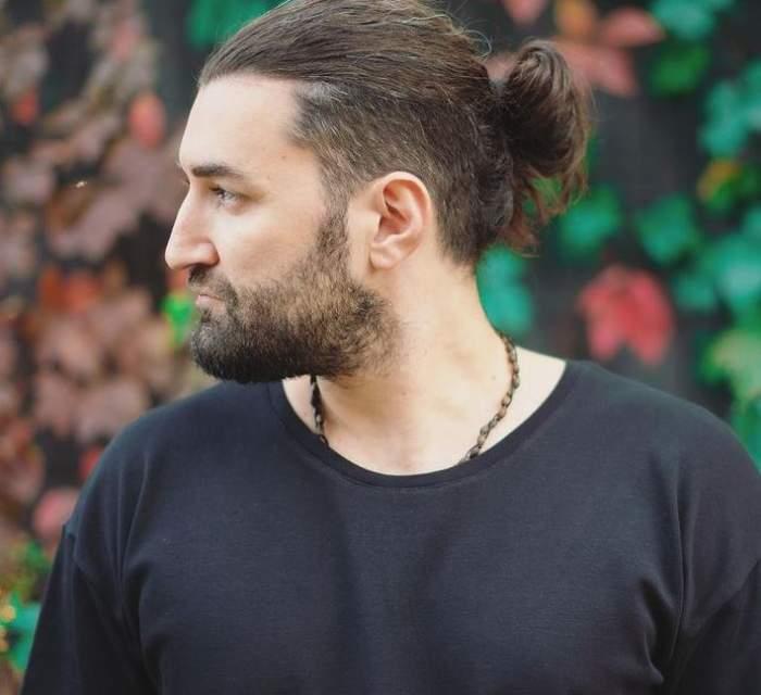 Smiley poartă tricou negru și are părul prins în coadă. Artistul privește într-o parte.