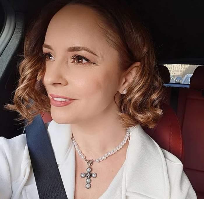 Andreea Marin își face un selfie din mașină, zâmbind. Vedeta poartă palton alb și centura de siguranță.