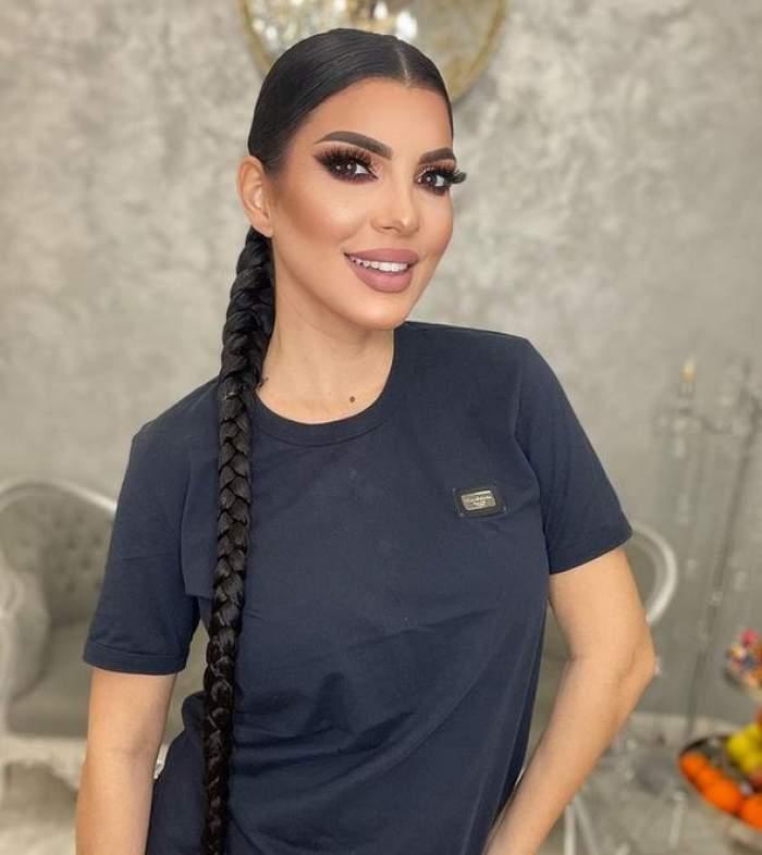 Andreea Tonciu poartă un tricou negru. Vedeta zâmbește larg și are părul prins într-o coadă împletită.