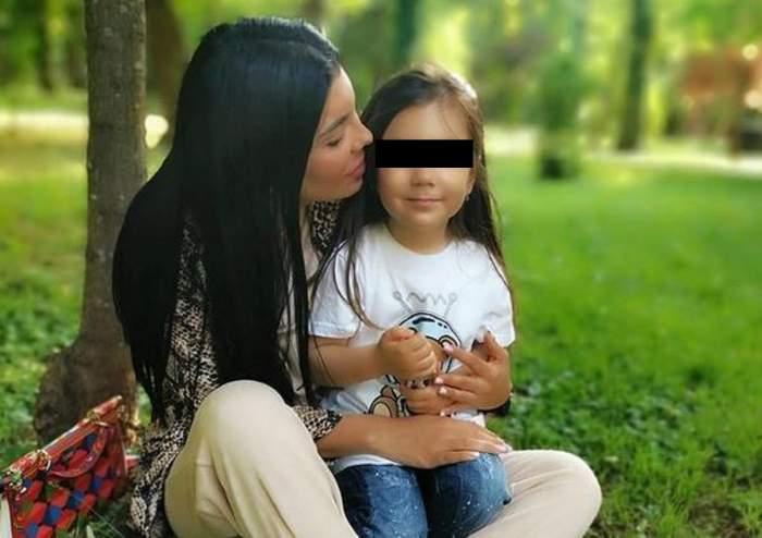 Andreea Tonciu și fiica ei, Rebecca, stau pe iarbă, în parc. Vedeta o ține în brațe. Micuța poartă blugi și tricou alb și are telefonul în mână.