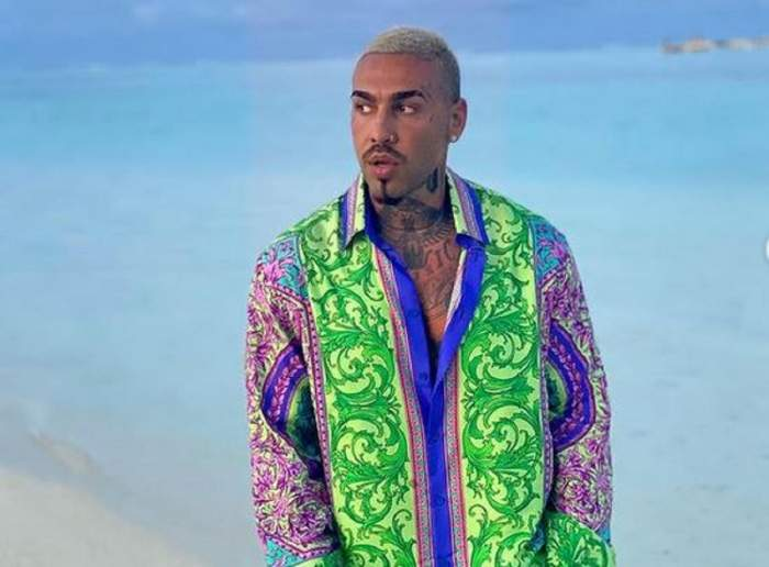 Alex Velea e pe plajă. Artistul poartă o cămașă colorată în nuanțe de verde, albastru, galben și roz și are gura întredeschisă.