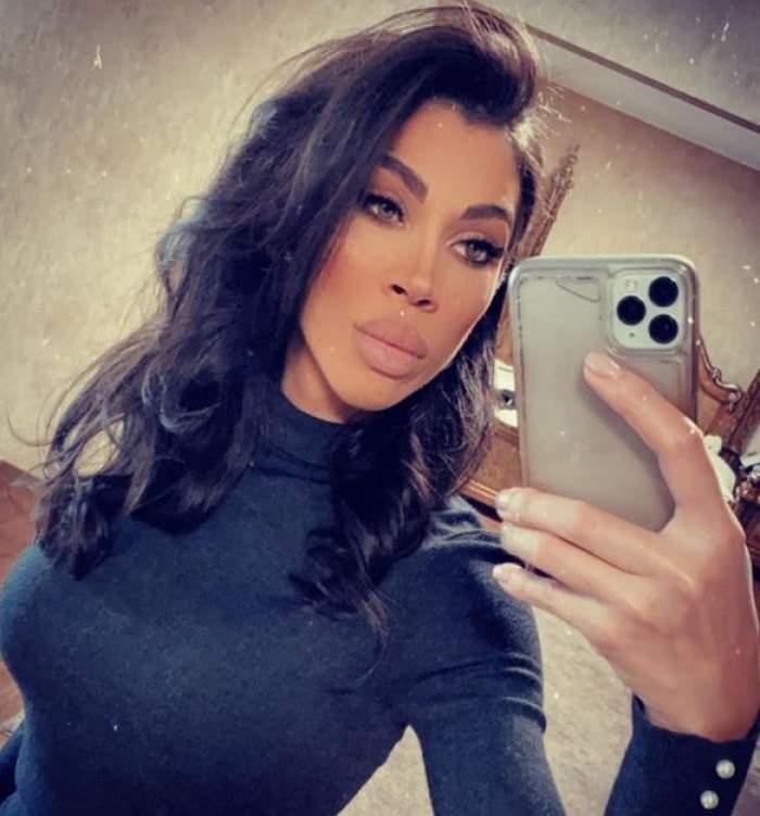 Raluca Pascu poartă o maletă neagră. Vedeta își face o poză cu telefonul în oglindă.