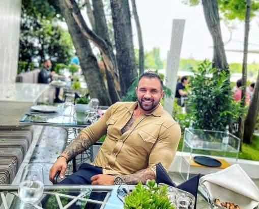 Alex Bodi cu tricou maro, la terasă.