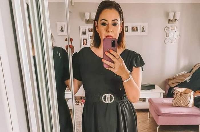 Oana Roman poartă rochie neagră și-și face poză cu telefonul.