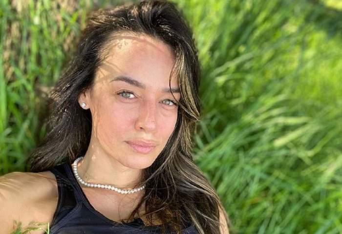 Andreea Raicu își face un selfie din iarbă și poartă maiou negru.