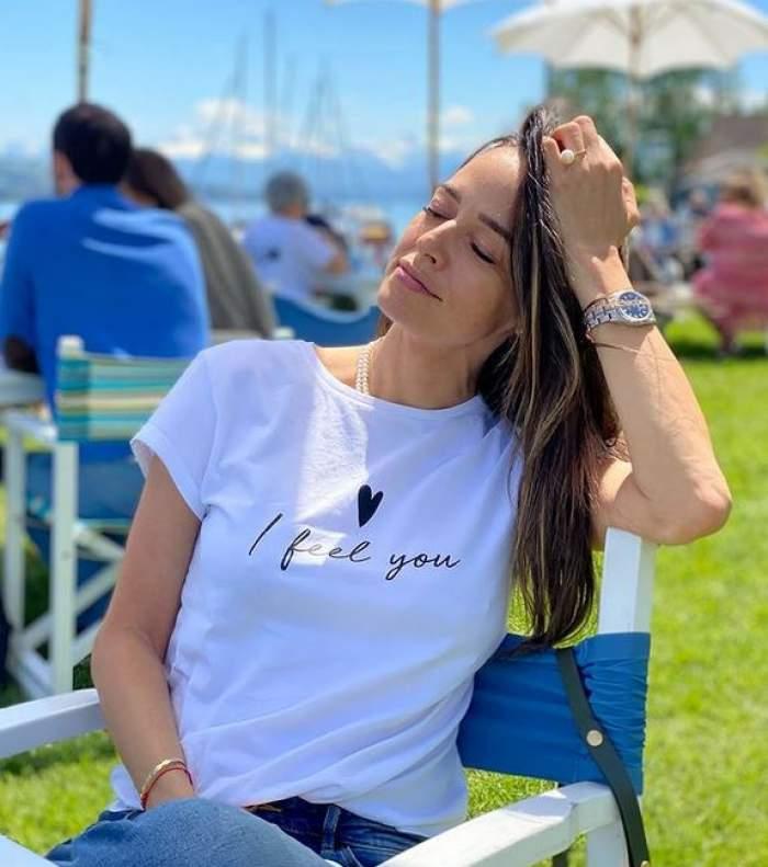 Andreea Raicu stă pe scaun la terasă și poartă blugi și tricou alb. Vedeta își ține o mână prin păr.