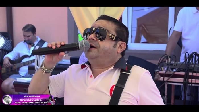 Adrian Minune în timp ce cântă, cu ochelari de soare la ochi.